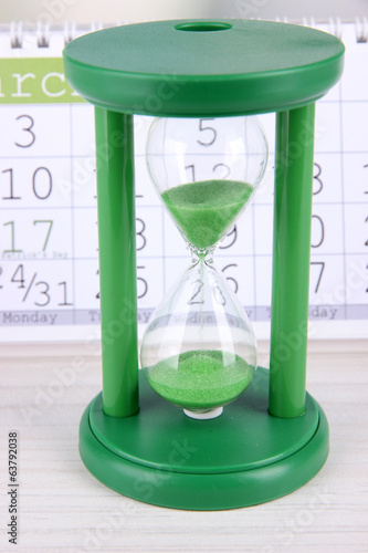 Hourglass and calendar close-up