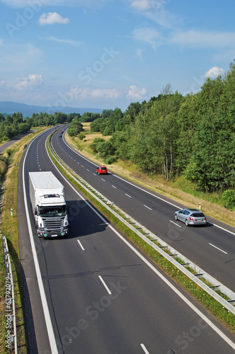 Highway passing through the countryside, truck and cars