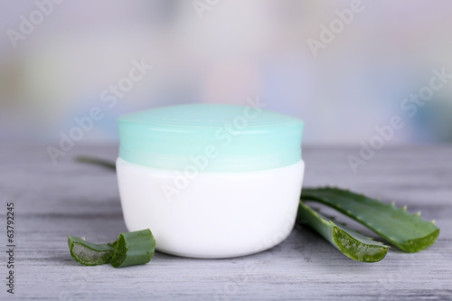 Cream and fresh green aloe leaves on wooden table