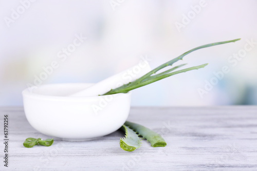 Fresh green aloe leaves in wooden mortar  on wooden table