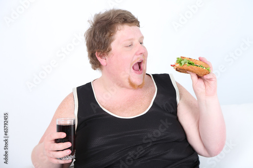 Fat man eating tasty sandwich and drink coke