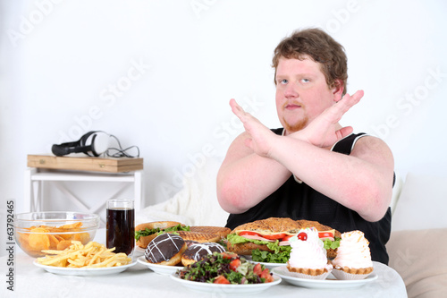 Fat man  do not want to eat a lot of unhealthy food,