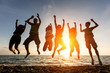 Leinwanddruck Bild - Multiracial Group of People Jumping at Beach, Backlight
