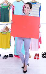 Beautiful young woman holding blank poster near rack with