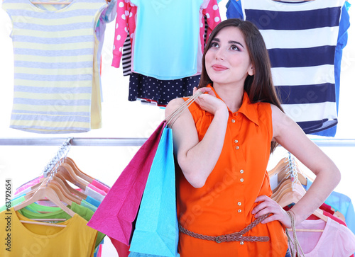 Beautiful young woman with paper bags near rack with hangers