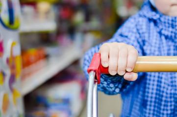 Little child hand holding shopping cart, blue jacket