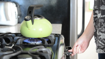 Person places tea kettle on stove, close up