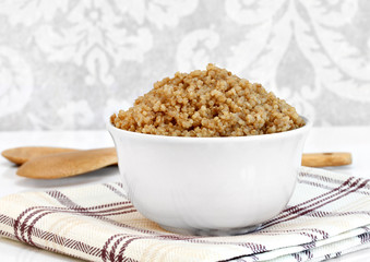 Cooked whole wheat quinoa in a bowl.  Macro with copy space.