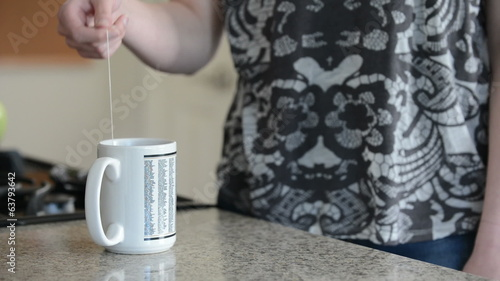 Woman steeping cup of tea