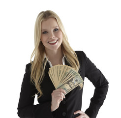 Confident young businesswoman holding currency notes and smiling