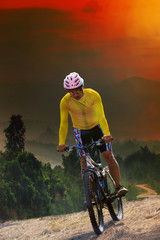 young man riding mountain bike bicycle crossing mountain hill ju