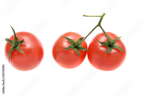 Three tomatoes on a branch isolated.