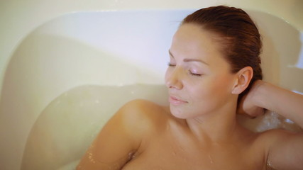 Young, attractive woman is lying in the bath