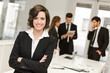 Business leader looking at camera in working environment - 63795831