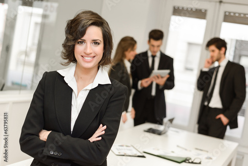 Business leader looking at camera in working environment poster