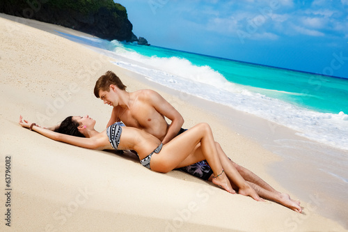 young loving happy couple on tropical beach, laying on sand