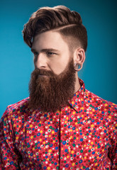 Stylish man with beard on blue background