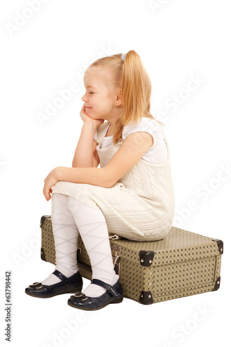 Small traveler girl sitting on suitcase