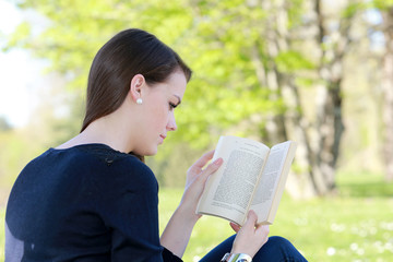 Jeune femme brune lisant assise dans un jardin