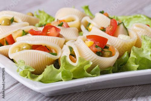 Italian pasta lumakoni stuffed salad of fresh vegetables closeup