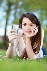 Jeune femme allongée écoutant son baladeur numérique