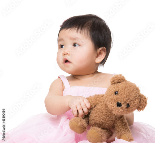 Asia baby girl looking aside and play with doll