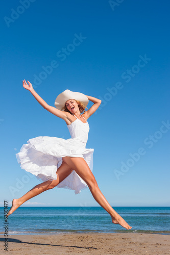 Young woman in white dress on the beach