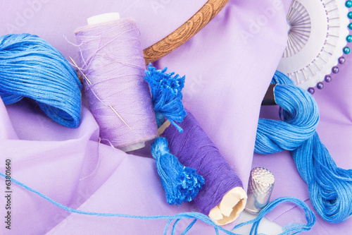 Embroidery tools, thread, needle, hoop and fabric in violet