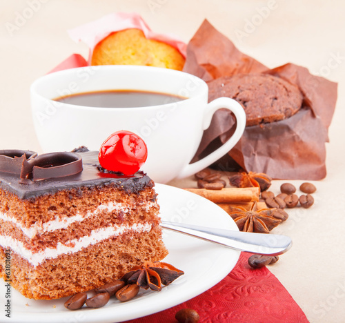 Chocolate cherry cake and cup of coffee with cupcake