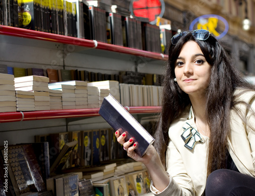 young girl holding a book inside library