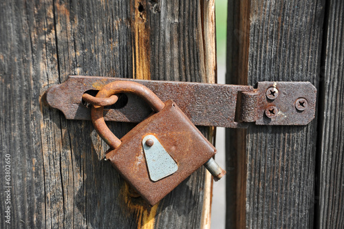 Rusty lock on old vintage rural wooden gate