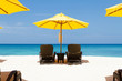 Yellow sun umbrellas and chairs on beach