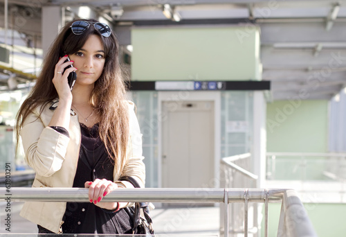 young girl at phone waiting to to the metro