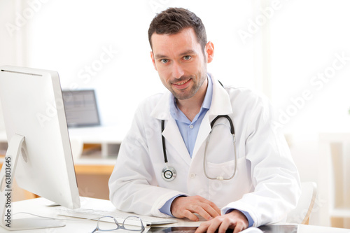 Portrait of a young smiling doctor in his office