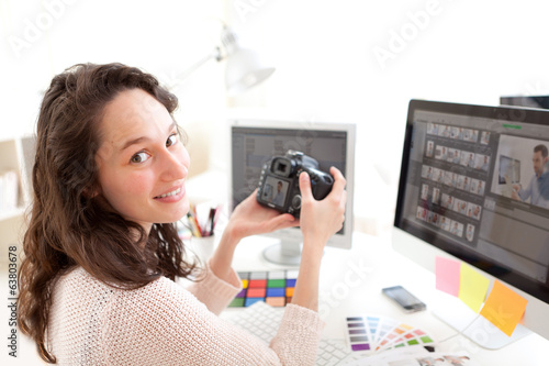 Young woman photographer watching pictures on camera