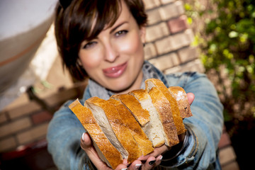 Young woman offering fresh sliced bread