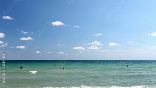 Beach with sand and blue water with waves with swimming people