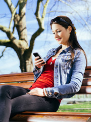 Beautiful woman using smartphone on park bench
