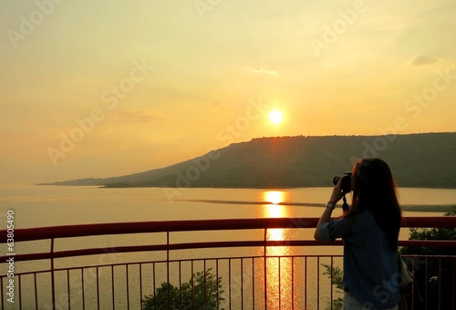 A woman photographs beautiful sunset at a reservoir