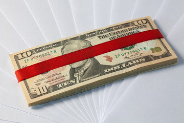 Pack of dollar bills with red ribbon