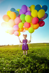 Happy little girl holding colorful balloons. Child playing on a