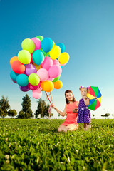 Beautiful little girl with mother colored balloons and rainbow u