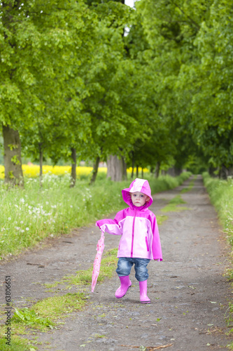 little girl wearing rubber boots with ubrella in spring alley
