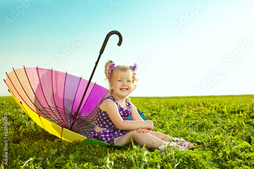 Beautiful little girl with rainbow umbrella on the grass in the