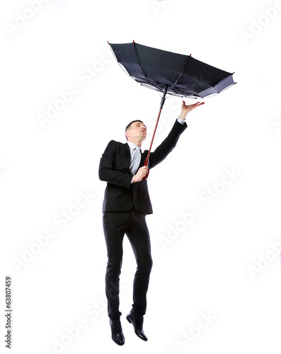 Businessman with umbrella fighting with strong wind