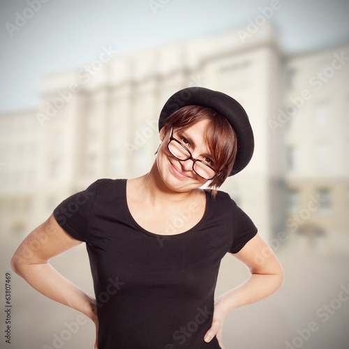 young woman in hat and glasses smiling