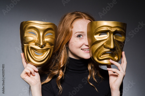 Redhead woman iwith mask in hypocrisy consept against grey backg
