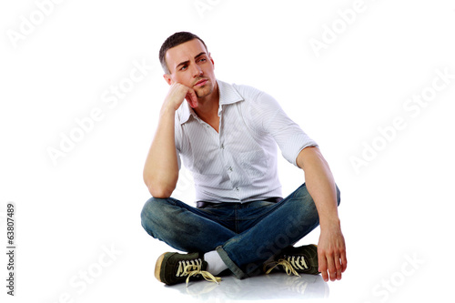 Pensive man sitting at the floor over white background