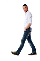 Side view portrait of a casual man walking over white background