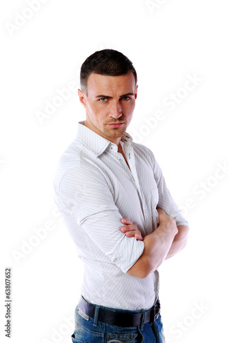 Portrait of a serious man with arms folded over white background